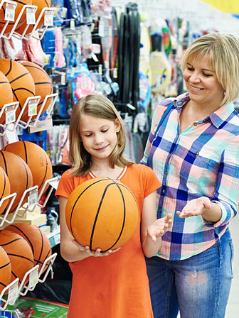 mother and daughter shopping for a basketball in a sporting goods store