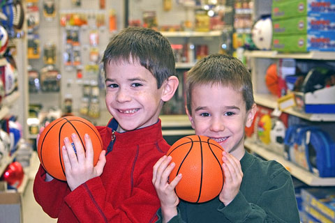 two boys holding basketballs in a sporting goods store